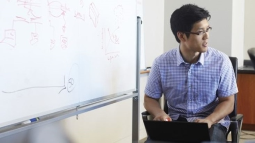 Man sitting by a whiteboard with a device