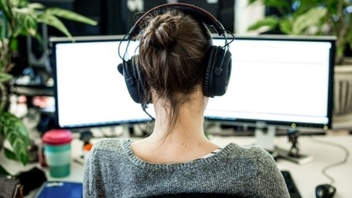 Woman at desk with two screens and headphones