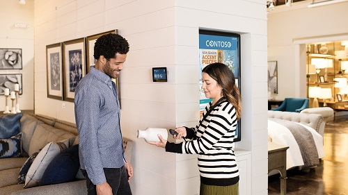 A retail worker demonstrating an embedded/IoT device